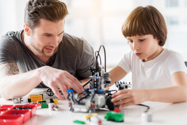 Concentrated little boy is making robot with help of adult man. They are sitting near table in workshop