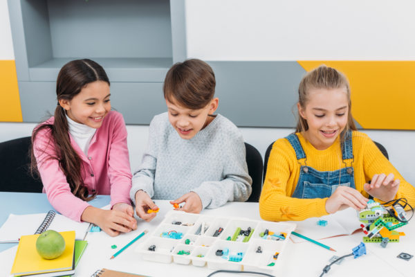 happy children sitting at desk and constructing robot in stem education class